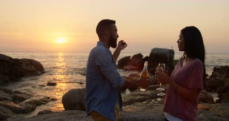 comprimento total : mixed-race Couple having champagne while standing on rock at beach. mixed-race Couple having fun at beach during sunset 4k Stock Footage