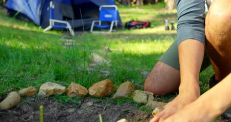 ajoelhado : Man preparing bonfire in the forest on a sunny day. Man holding stone 4k Stock Footage