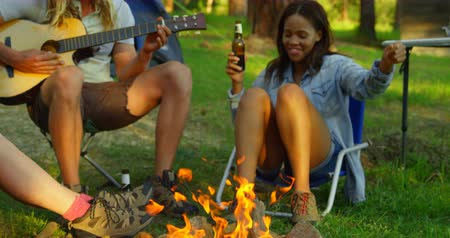 comprimento total : Friends having fun near bonfire in the forest. Friends camping together 4k Stock Footage