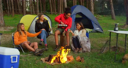 костра : Friends having coffee near campfire in the forest. Friends camping together in the forest 4k