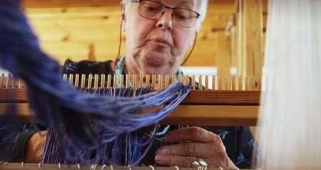 závit : Low angle view of old caucasian senior woman preparing and sitting at hand loom machine in a workshop. She is wrapping thread on the beam 4k