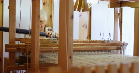 szakértő : Front view of old caucasian senior woman weaving cloth on handloom machine in a workshop. She is using cotton thread 4k Stock mozgókép