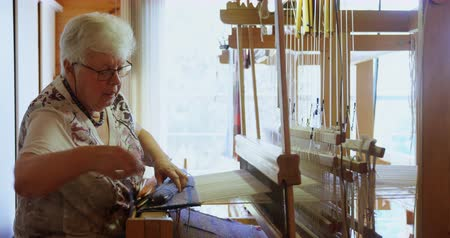 závit : Side view of old caucasian senior woman weaving cloth on handloom machine in a workshop. She is using cotton thread 4k