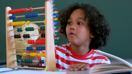 aritmética : Front view of African American schoolboy learning mathematics with abacus at desk in a classroom. He is counting beads 4k