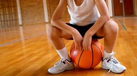 basketbalveld : Front view of athletic African American schoolboy sitting on basketball in basketball court at school. She is smiling and looking at camera 4k Stockvideo