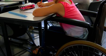 одноклассник : Side view of disabled blonde Caucasian schoolgirl studying at desk in classroom at school. She is writing on notebook 4k