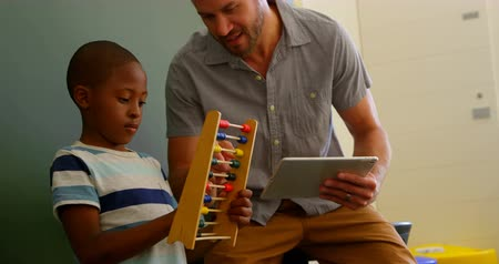 aritmética : Front view of young Caucasian male teacher teaching schoolboy to use abacus in classroom. Teacher holding digital tablet 4k