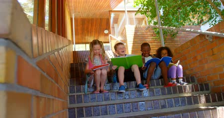 conveniente : Front view of diverse group of school children reading book while sitting on stairs of elementary school. They are studying together 4k Stock Footage