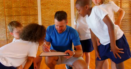 panoya : Front view of Caucasian male sport teacher and group of diverse schoolkids discussing over clipboard in the basketball court. They are listening to sports teacher 4k