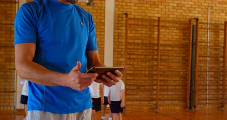 diverso : Front view of young Caucasian basketball coach using digital tablet in basketball court at school. Schoolkids playing in the background 4k Stock Footage