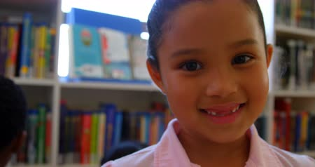 akademický : Front view of happy cute mixed race schoolgirl standing in school library. She is smiling and looking at camera 4k Dostupné videozáznamy