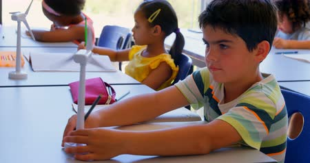 schoolkid : Front view of group of diverse studious schoolkids studying at desk in the classroom at school. They are looking at wind turbines 4k