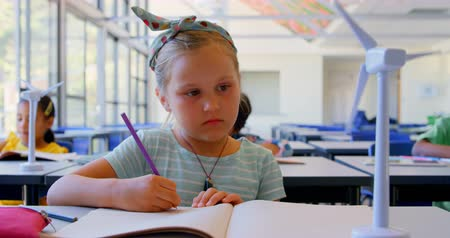 scolari : Front view of Caucasian schoolgirl writing in notebook at desk in classroom. She is looking at model wind turbine 4k Filmati Stock