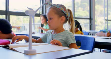 schoolkid : Front view of Caucasian schoolgirl studying while the wind turbine spins at desk in classroom. She is operating wind turbine 4k