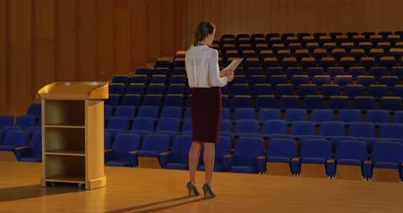 assentos : Rear view of young Caucasian businesswoman practicing speech in empty auditorium.She is standing and gesturing 4k