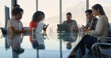 working together : Front view of diverse business executives sitting at table and working in modern office. They are using multimedia device 4k Stock Footage