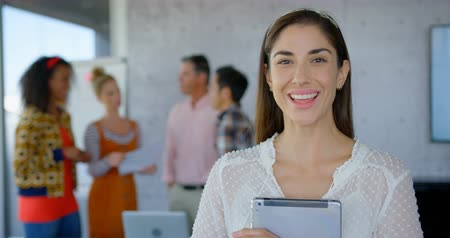 standing at table : Front view of happy young Caucasian female holding a digital tablet and looking at camera while others people talking each others in background 4k