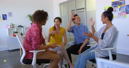sofisticado : Front view of happy multi-ethnic business colleagues giving high five to each other in modern office. They are working together 4k Vídeos