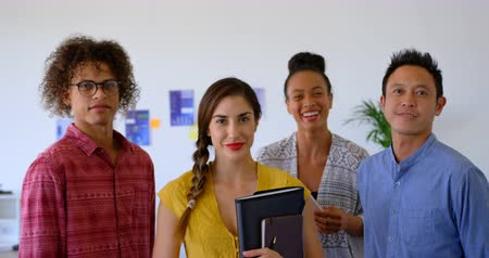 sofisticado : Portrait of happy young multi-ethnic business colleagues standing together in modern office. They are smiling and looking at camera 4k