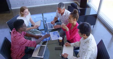sofisticado : High angle view of multi-ethnic business colleagues discussing over graphs in a meeting at modern office. They are working together in office 4k Stock Footage