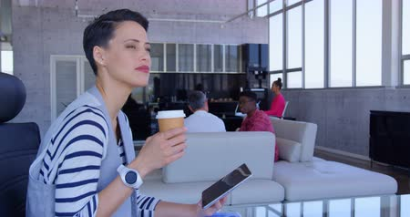 inclusive : Side view of Beautiful Caucasian Businesswoman using digital tablet while drinking coffee in modern office. Multi-ethnic oworkers working in the background 4k