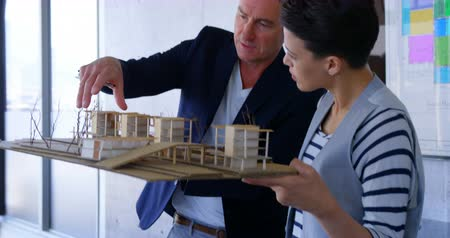 working together : Front view of Caucasian business people discussing over factory model in modern office. They are holding the factory model 4k