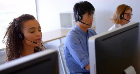 рабочий стол : Side view of young multi-ethnic customer sales executives talking on headset in modern office. They are working together at desk 4k Стоковые видеозаписи