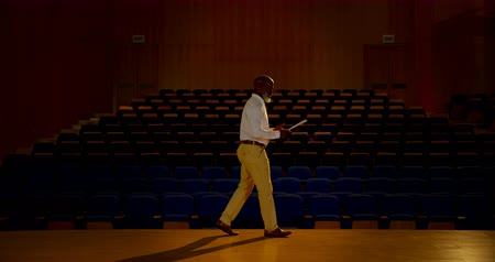 assentos : Side view of senior African American businessman practicing speech in empty auditorium. He is walking and gesturing 4k
