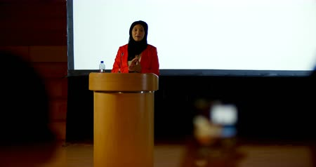 theater hall : Front view of beautiful mature Caucasian hijab businesswoman speaking at podium in auditorium. She is gesturing and clasped hands 4k