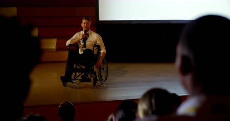 lugares sentados : Front view of handsome young Caucasian disabled businessman speaking in business seminar in auditorium. He is sitting on wheelchair 4k