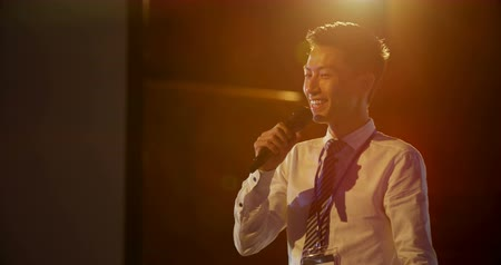 assentos : Front view of handsome young Asian businessman speaking in business seminar at auditorium. He is holding microphone 4k Stock Footage