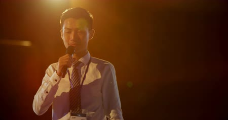 hangszóró : Front view of handsome young Asian businessman speaking in business seminar at auditorium. He is holding microphone 4k Stock mozgókép