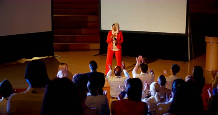 inclusive : Front view of beautiful happy mature Caucasian hijab businesswoman standing on stage in business seminar. Audience standing and applauding 4k