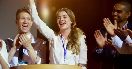 theater hall : Front view of happy multi-ethnic business people applauding young businesswoman on stage in seminar. Businesswoman smiling and cheering 4k