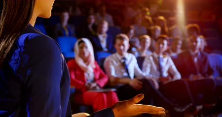 inclusive : Rear view of young mixed race businesswoman speaking in business seminar at auditorium. Audience listening her 4k