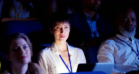 assentos : Front view of young Asian businesswoman sitting with laptop in business seminar at auditorium. She smiling and looking 4k