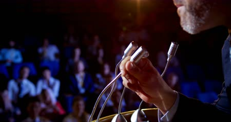 lecture : Mid section of mature Caucasian businessman speaking in business seminar on stage in auditorium. He is holding microphone 4k Stock Footage