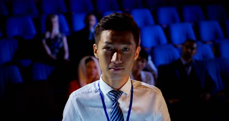 assentos : Front view of young Asian businessman attending business seminar in auditorium. He is looking at camera 4k