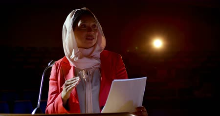 подиум : Front view of mature mixed race businesswoman with hijab speaking in business seminar at auditorium. She is reading script 4k