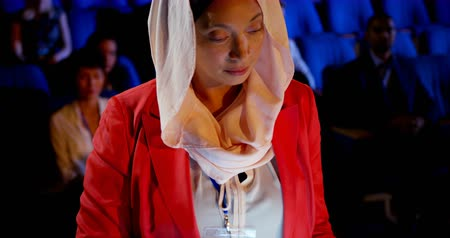 スクローリング : Front view of mature mixed race businesswoman with hijab using digital tablet at seminar in auditorium. She is smiling and looking at camera 4k