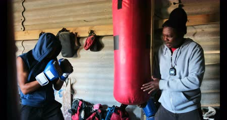 rehberlik : Side view of young African American male boxer practicing boxing with trainer in fitness studio. He is hitting punching bag 4k Stok Video