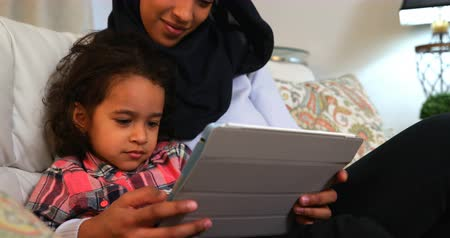 невинность : Front view of a young Asian mother wearing a hijab and using a digital tablet with her daughter on the sofa at home 4k