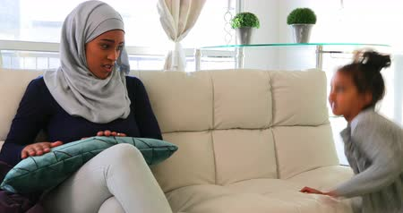mischief : Front view of a young Asian mother wearing the hijab and playing with her daughter in the living room 4k