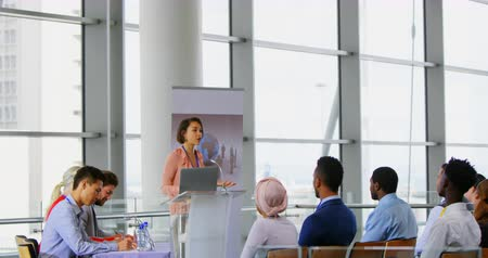 hangszóró : Side view of an Asian female speaker standing on the podium with her laptop and speaking to the public in a business seminar 4k Stock mozgókép