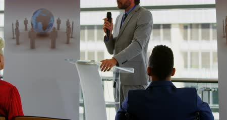 trabalho em equipe : Side view of a Caucasian male speaker speaking to the public while standing on the podium in the business seminar 4k Vídeos
