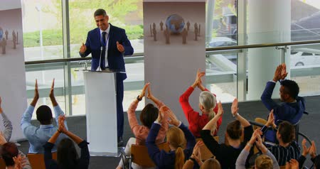 inclusive : High angle view of a Caucasian male speaker standing on the podium while being applause by the public in the business seminar 4k