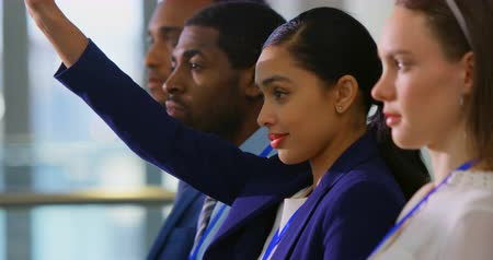 подиум : Side view of a beautiful mixed-race businesswoman raising hand and asking a question in the business seminar 4k Стоковые видеозаписи