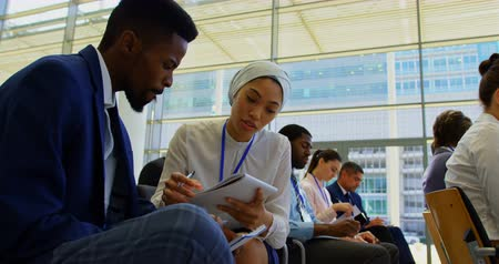 rehberlik : Side view of young multi ethnic business people discussing over a notepad while attending a business seminar 4k Stok Video
