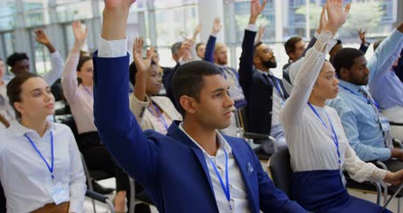 questionnement : Side view of multi ethnic business people sitting and raising hands in the business seminar 4k