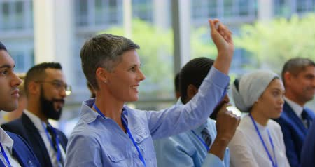 inclusive : Side view of Caucasian businesswoman raising hand  and standing up in the public in a business seminar 4k Stock Footage